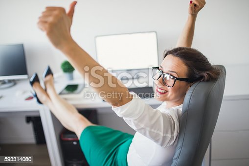 Excited woman raising her arms while working on computer in her office