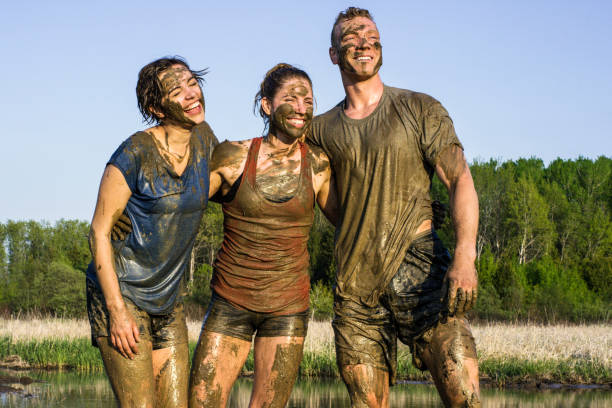 Victory Three young adult athletes are are celebrating victory after an extreme challenge of running through mud outdoors. mud run stock pictures, royalty-free photos & images