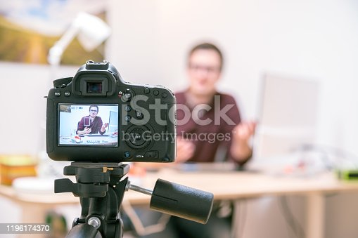 Camera on a tripod filming a blogger at home sitting on his workspace