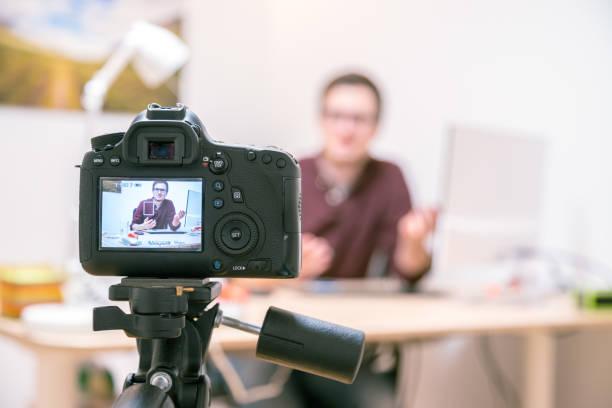 video blogger at home: camera op statief is het filmen van een jonge man zittend op zijn werkplek - spiegelreflexcamera stockfoto's en -beelden