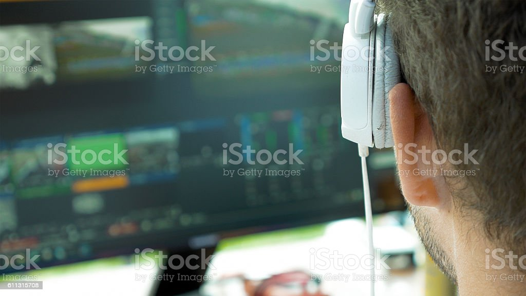 Video broadcast editor with headphones at screen - Photo