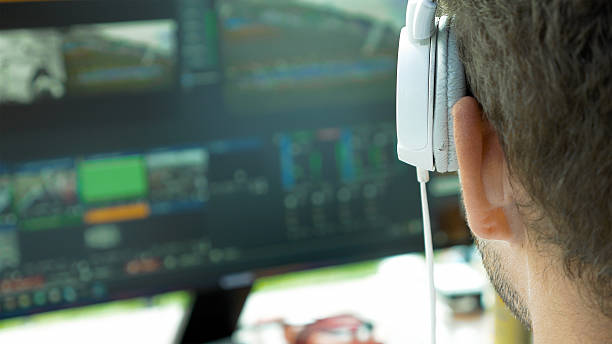 Video broadcast editor with headphones at screen stock photo