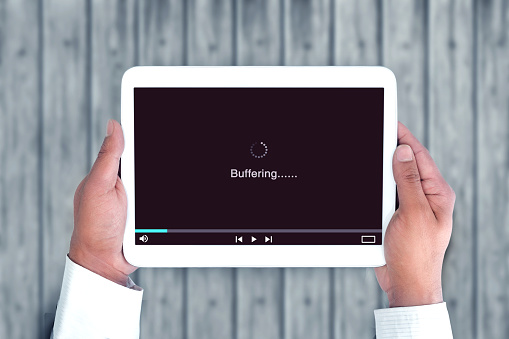 Hand holding tablet pc watching online video but it is buffering due to slow internet