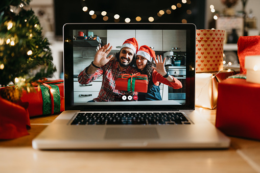 Video call on a laptop screen during Christmas. Celebrating Christmas holidays during Coronavirus Covid-19 pandemic concept. Social distancing concept.