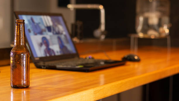 Video call on laptop prepared on a kitchen counter with friends from home with a beer in the foreground stock photo