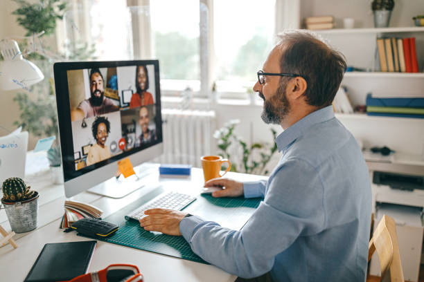 Video call with team members Businessman discussing work on video call with team members video call stock pictures, royalty-free photos & images