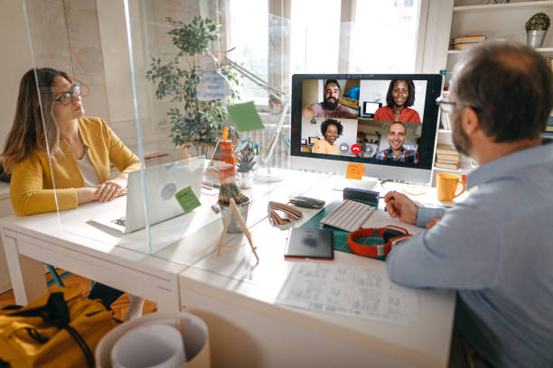 Video call with team members Businessman and businesswoman discussing work on video call with team members through glass partition at office social distancing stock pictures, royalty-free photos & images