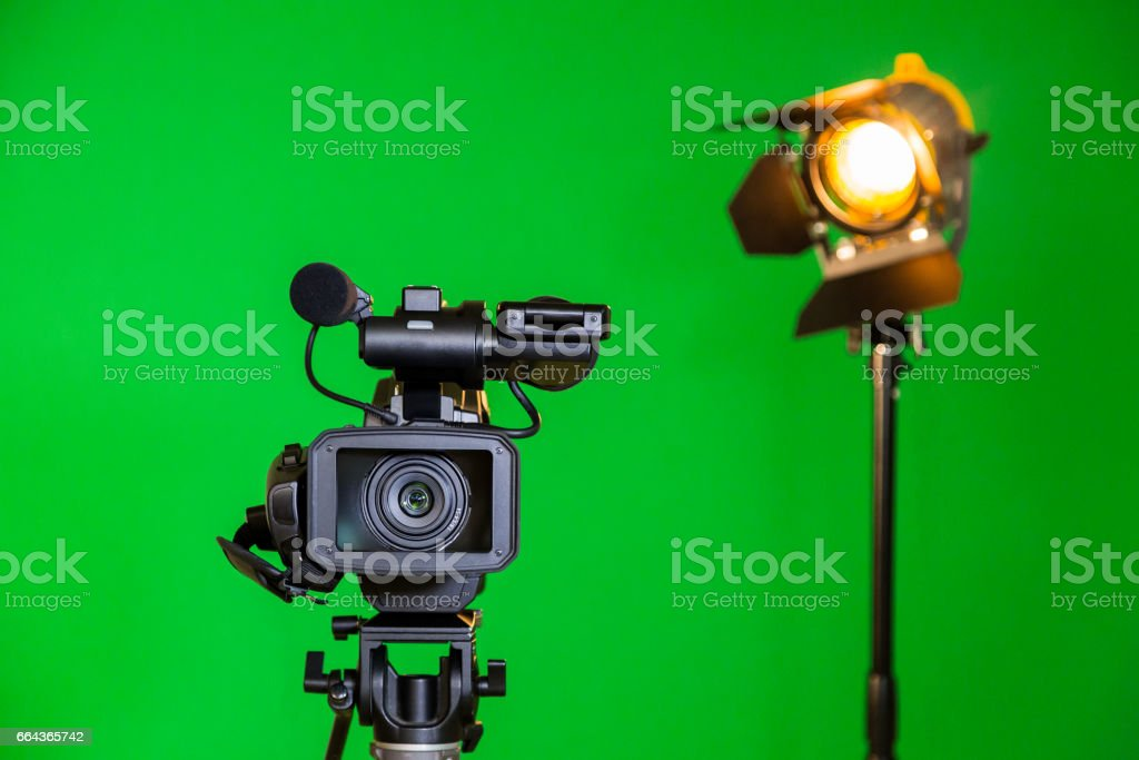 A video camera and a spotlight with a Fresnel lens on a green background. Filming in the interior. The chroma key stock photo