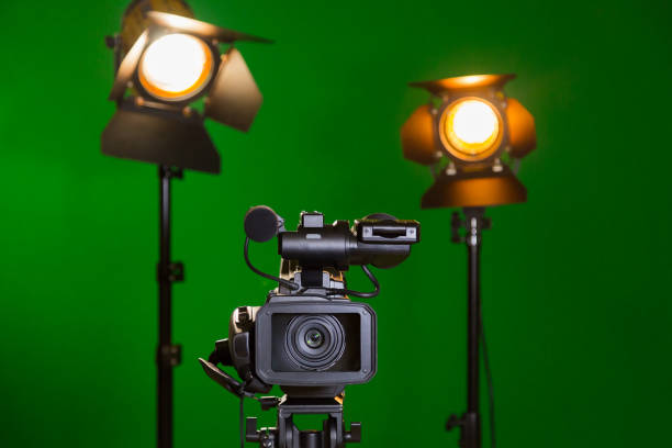A video camera and a spotlight with a Fresnel lens on a green background. Filming in the interior. The chroma key