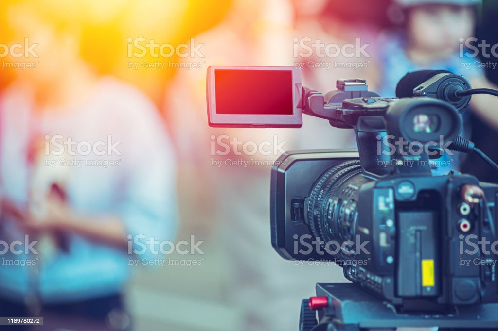 Video camera camcorder operator working at live event broadcasting blue color tone. Video camera camcorder operator working at live event broadcasting blue color tone. Director Stock Photo