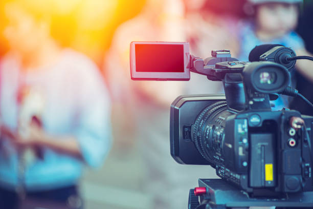 Video camera camcorder operator working at live event broadcasting blue color tone. Video camera camcorder operator working at live event broadcasting blue color tone. analogue audio storage media stock pictures, royalty-free photos & images