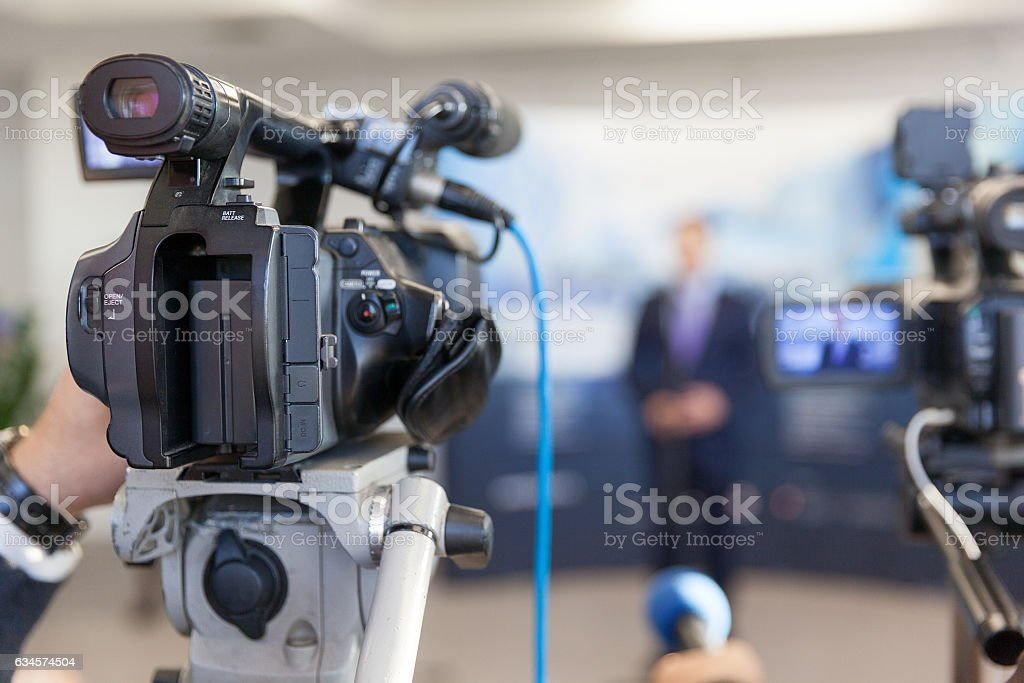 Video camera in focus, blurred spokesman in background stock photo