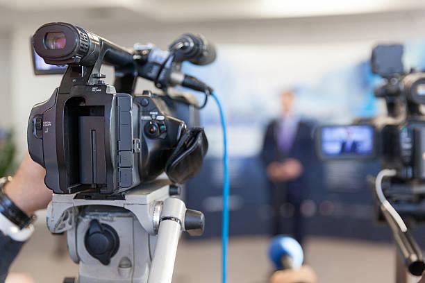 Video camera in focus, blurred spokesman in background stock photo