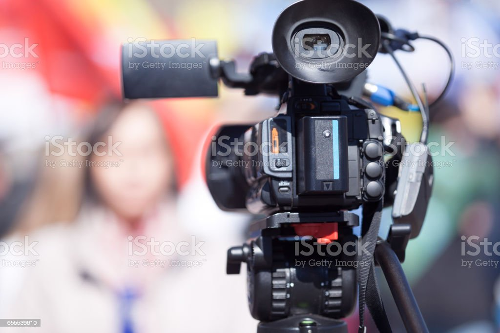 Video camera in the focus, blurred female reporter in the background. Television broadcasting. royalty-free stock photo