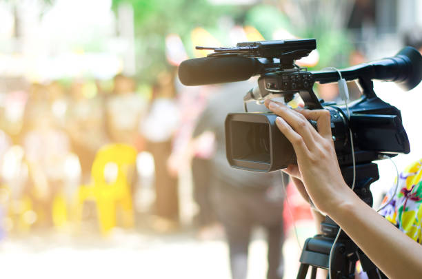 Video camera operator working with his equipment, blurred background stock photo
