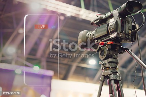 istock Video camera taking live video streaming with lighting frame of mobile phone and Live text at meeting room. 1224887156