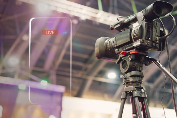 câmera de vídeo fazendo transmissão de vídeo ao vivo com moldura de iluminação do celular e texto ao vivo na sala de reunião. - live - fotografias e filmes do acervo