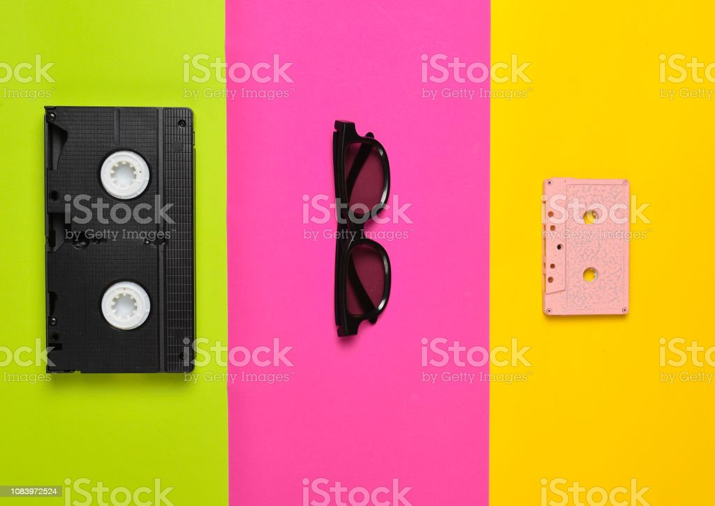 Video cassette, sunglasses, audio cassette on a multi-colored paper background. Minimalist trend, flat lay, top view. – zdjęcie
