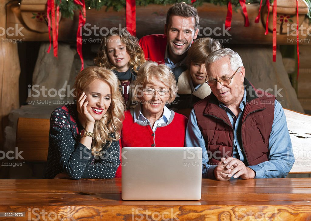 Video chat during Christmas Multi generation family: grandparents, parents and children sitting at the table at home and having video chat.  Active Seniors Stock Photo