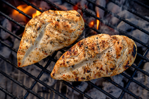 Deliciously marinated and seasoned chicken breasts on a charcoal grill