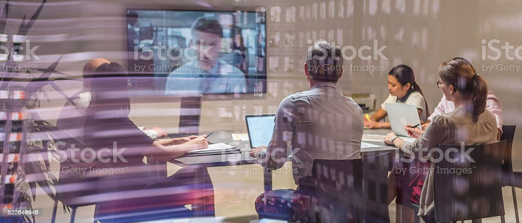 Video conference meeting Business people sitting and discussing in board room during video conference meeting. 25-29 Years Stock Photo