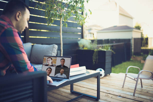 Video conferencing from his backyard stock photo