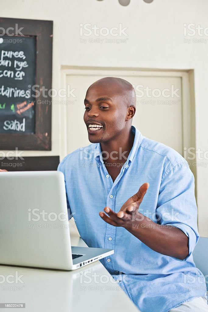 Video conversation Man using laptop in cafe and having video conversation. Adult Stock Photo