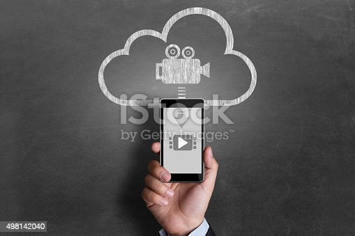 Close-up of a man holding a mobile phone on cloud computing icon with downloading video on mobile phone from cloud server representing the concept of cloud computing.