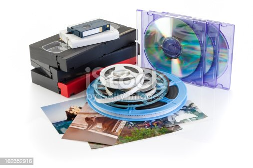 Video cassettes, photographs and film reels on white background with DVD, Concept for DVD transfer. +++Photographs shown were taken by photographer.++
