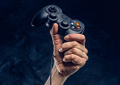 istock Video game console controller in gamer hand against the background of the dark wall 1180049184