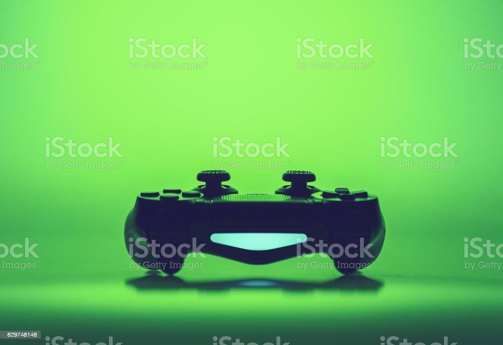 Videospiel-Joystick auf dem lebendigen grünen Hintergrund – Foto