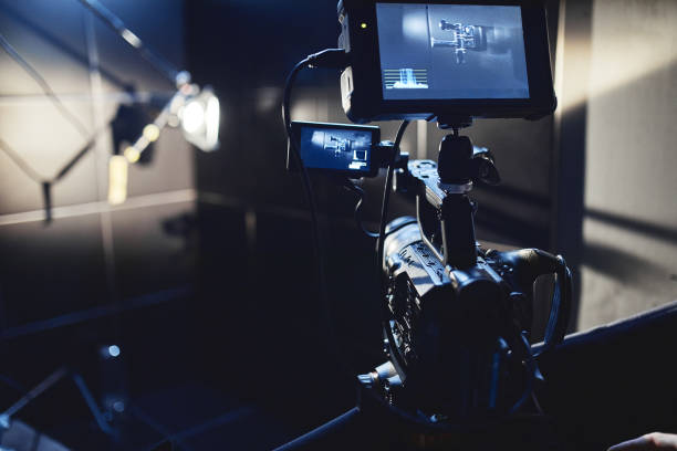 Video production backstage. Behind the scenes of creating video content, a professional team of cameramen with a director filming commercial ads. Video content creation, video creation industry. Low key, selective focus, film graine stock photo