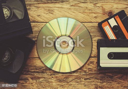 video tapes, audio tapes and compact disc on a wooden table