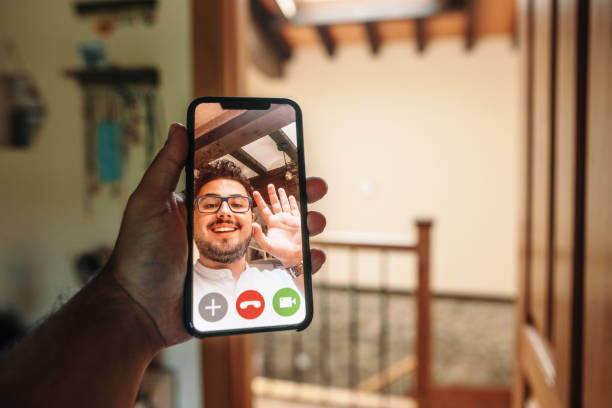 Videocall - Man waving on a smartphone screen stock photo