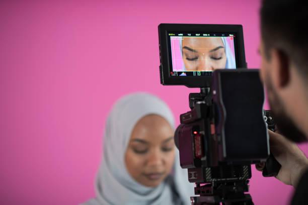 Videograf in rosa Studio Aufnahme Video auf professionelle Kamera von Schießen weibliche muslimische Frau – Foto