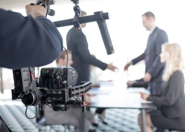 Videographer making video of business people stock photo