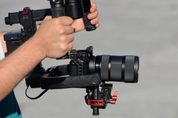 videograaf schiet video met mirrorless camera met stabilisator - spiegelreflexcamera stockfoto's en -beelden