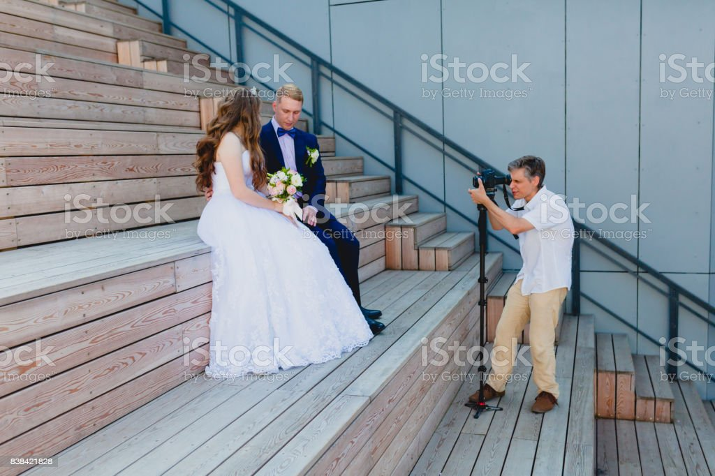 Videographer with Groom and Bride stock photo
