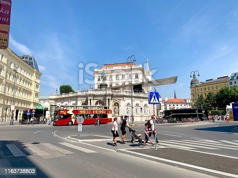 Vienna, Austria - July, 20 - 2019: Sightseeing bus in front of the equestrian statue of Emperor Franz Joseph I. Hot dog kiosk on the left, with a green rabbit on top. Behind the statue the Albertina building to be seen. In the foreground pedestrians crossing a street.
