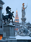 Vienna - Pallas Athena fountain and parliament in winter evening and Town hall tower in background