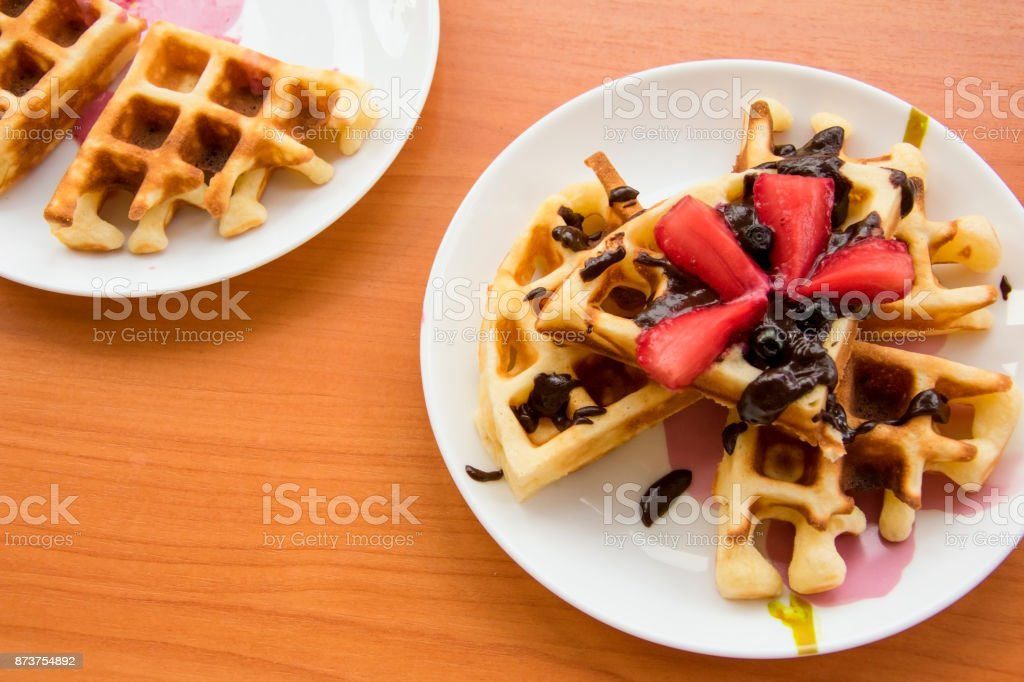 Viennese waffles with strawberries and chocolate on the plate stock photo