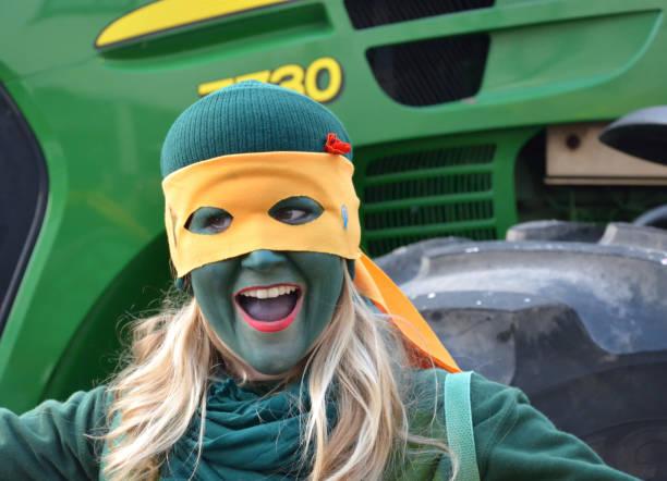 viersen-dülken, nordrhein westfalen, deutschland 16. februar 2015: junge frau mit einer grünen fläche und eine gelbe maske, breit lächelnd.  der jährliche karneval in deutschland. montag parade stieg. - karnevalskostüme köln stock-fotos und bilder