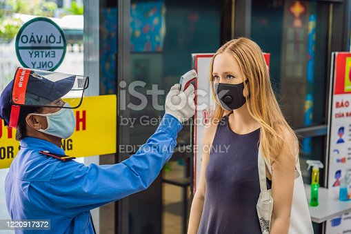 istock Vietnam, Nha Trang, 15.04.2020: Medical staff are checking the temperature of woman. Before entering the area with an epidemic Covid-19 1220917372