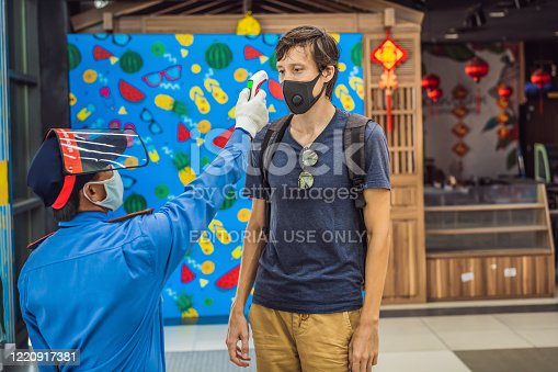 istock Vietnam, Nha Trang, 15.04.2020: Medical staff are checking the temperature of man. Before entering the area with an epidemic Covid-19 1220917381