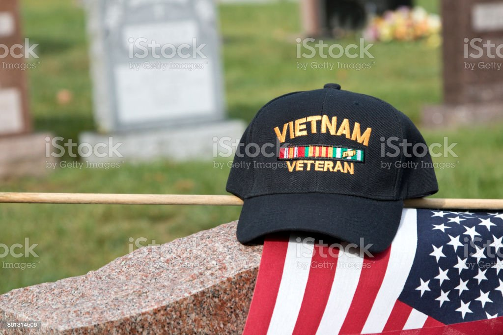 Vietnam Veteran's Cap sitting on a grave marker with American Flag in a cemetery with other gravestones in background stock photo