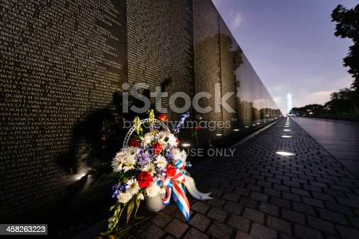 Washington, DC. USA - June 18, 2013: A flower bouquet in front of the Vietnam Veteran's Memorial with a view of the Washington Monument in the background.