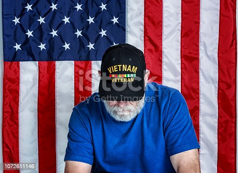 Authentic 68 year old United States Navy Vietnam War military veteran sitting looking down with his face partially covered. Copy space on the USA flag stars and stripes red, white and blue background. He is wearing an inexpensive, non-branded, generic, souvenir shop replica Vietnam veteran commemorative baseball hat style cap.