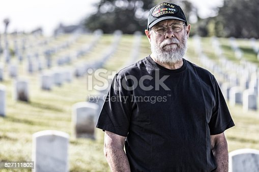 An authentic, 67 year old United States Navy Vietnam War military veteran is standing mourning among rows of grave markers in a military cemetery. He is looking at the camera with a solemn, sad facial expression. He is wearing a casual black t-shirt and an inexpensive, non-branded, generic, souvenir shop replica Vietnam veteran commemorative baseball cap style hat.