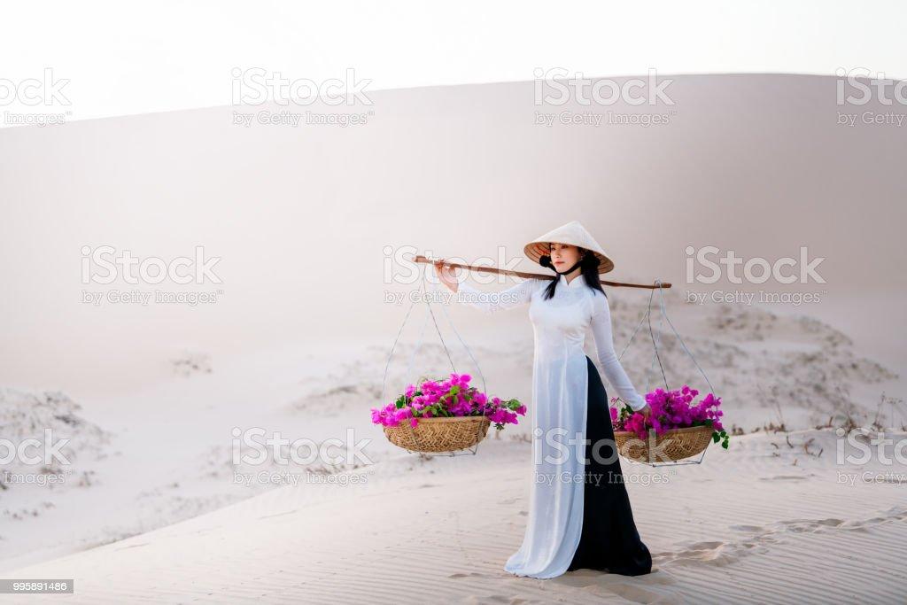 Vietnam Frau tragen Ao Dai Kultur Tracht am roten Sand. – Foto