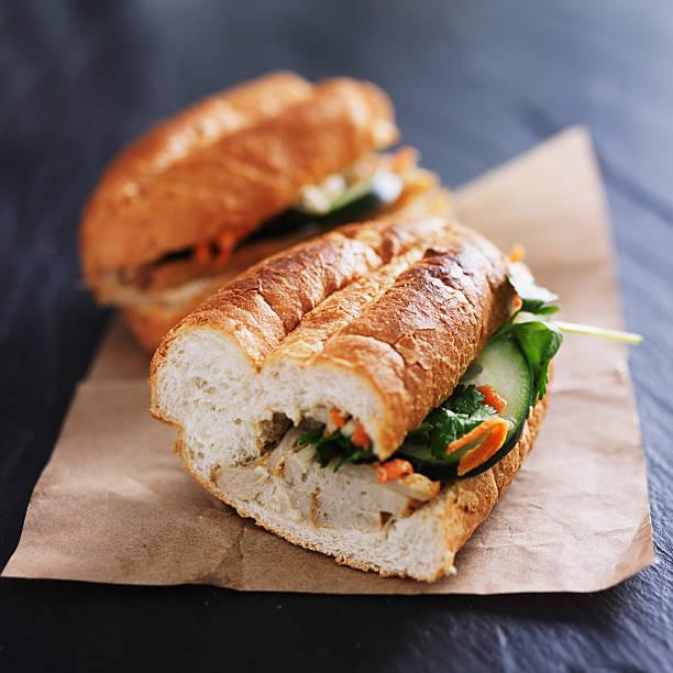 vietnamese bahn mi sandwich halves vietnamese bahn mi sandwich halves shot close up with steamed pork inside bánh mì sandwich stock pictures, royalty-free photos & images
